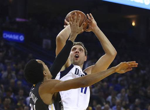 Dallas Mavericks' Dirk Nowitzki shoots against Golden State Warriors' Shaun Livingston during the first half of an NBA basketball game Thursday, Feb. 8, 2018, in Oakland, Calif.