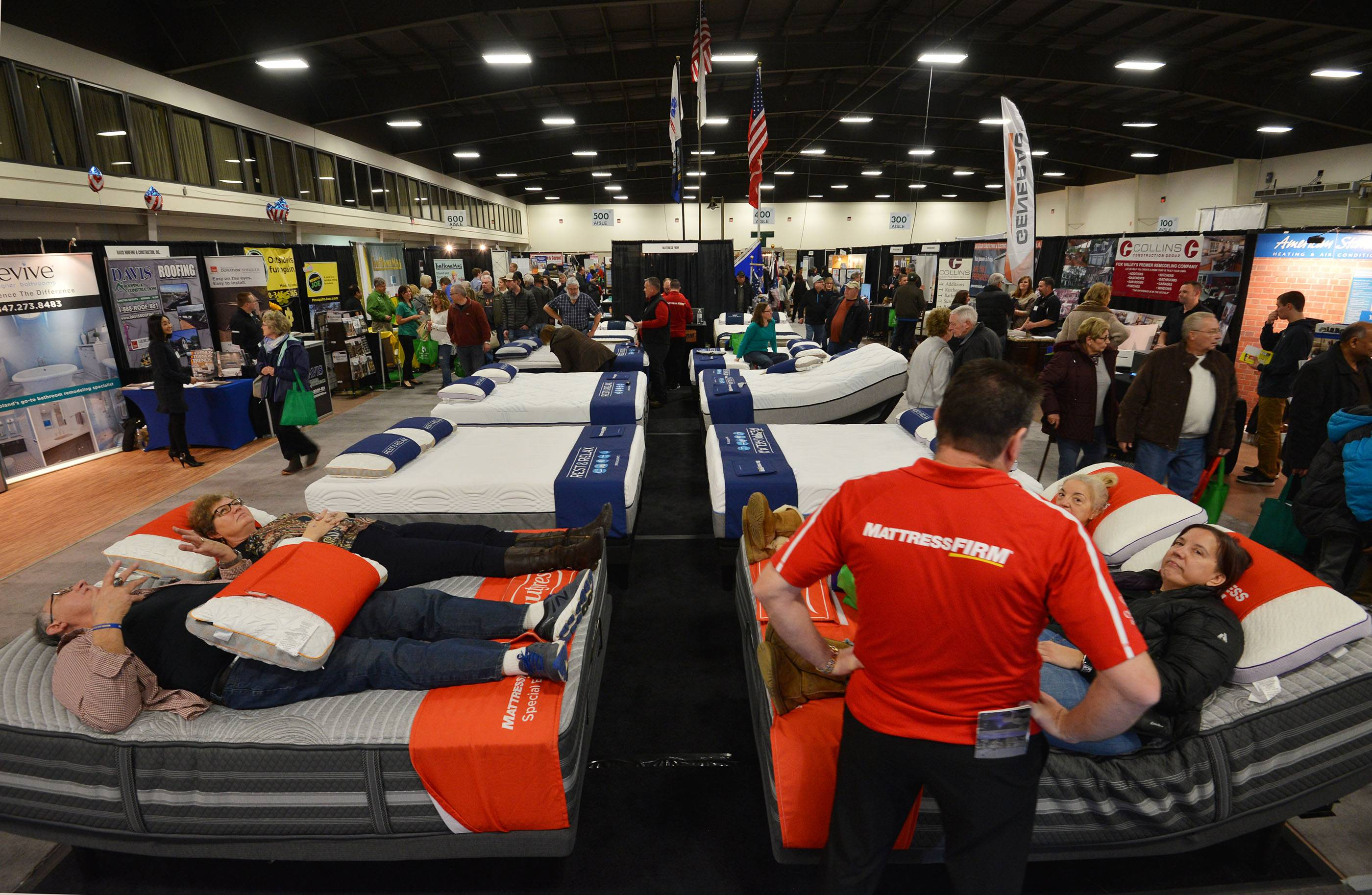 Shoppers try the mattresses at the Mattress FIRM display Saturday at the Old House New House Home Show in the Mega Center at Pheasant Run Resort in St. Charles.