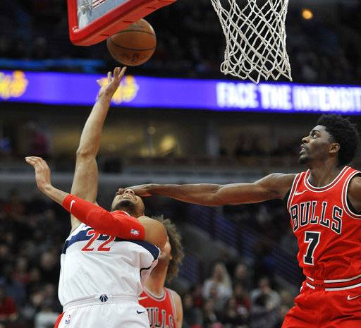 Washington Wizards' Otto Porter Jr. (22) goes up for a shot while being fouled by Chicago Bulls' Justin Holiday (7) during the first half of an NBA basketball game Saturday, Feb. 10, 2018, in Chicago.