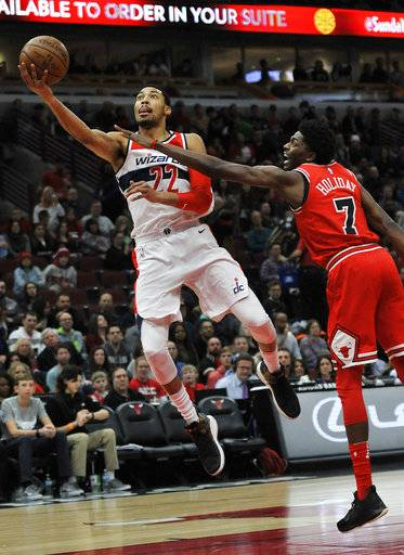 Washington Wizards' Otto Porter Jr. (22) goes up for a shot against Chicago Bulls' Justin Holiday (7) during the first half of an NBA basketball game Saturday, Feb. 10, 2018, in Chicago.
