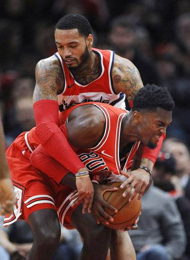 Chicago Bulls' Bobby Portis front, battles Washington Wizards' Mike Scott back, for a loose ball during the first half of an NBA basketball game Saturday, Feb. 10, 2018, in Chicago.