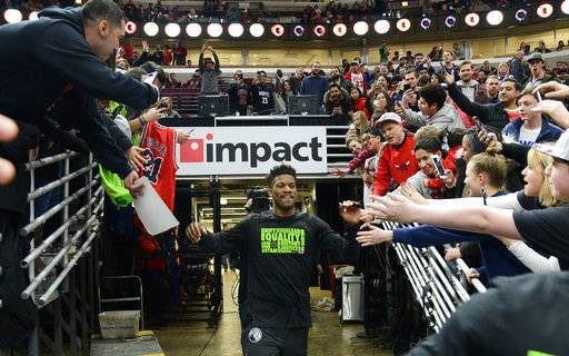 CORRECTS YEAR TO 2018 - Former Chicago Bulls player Jimmy Butler, center, greets fans as he heads onto the court as a member of the Minnesota Timberwolves before an NBA basketball game  against the Bulls, Friday, Feb. 9, 2018, in Chicago.