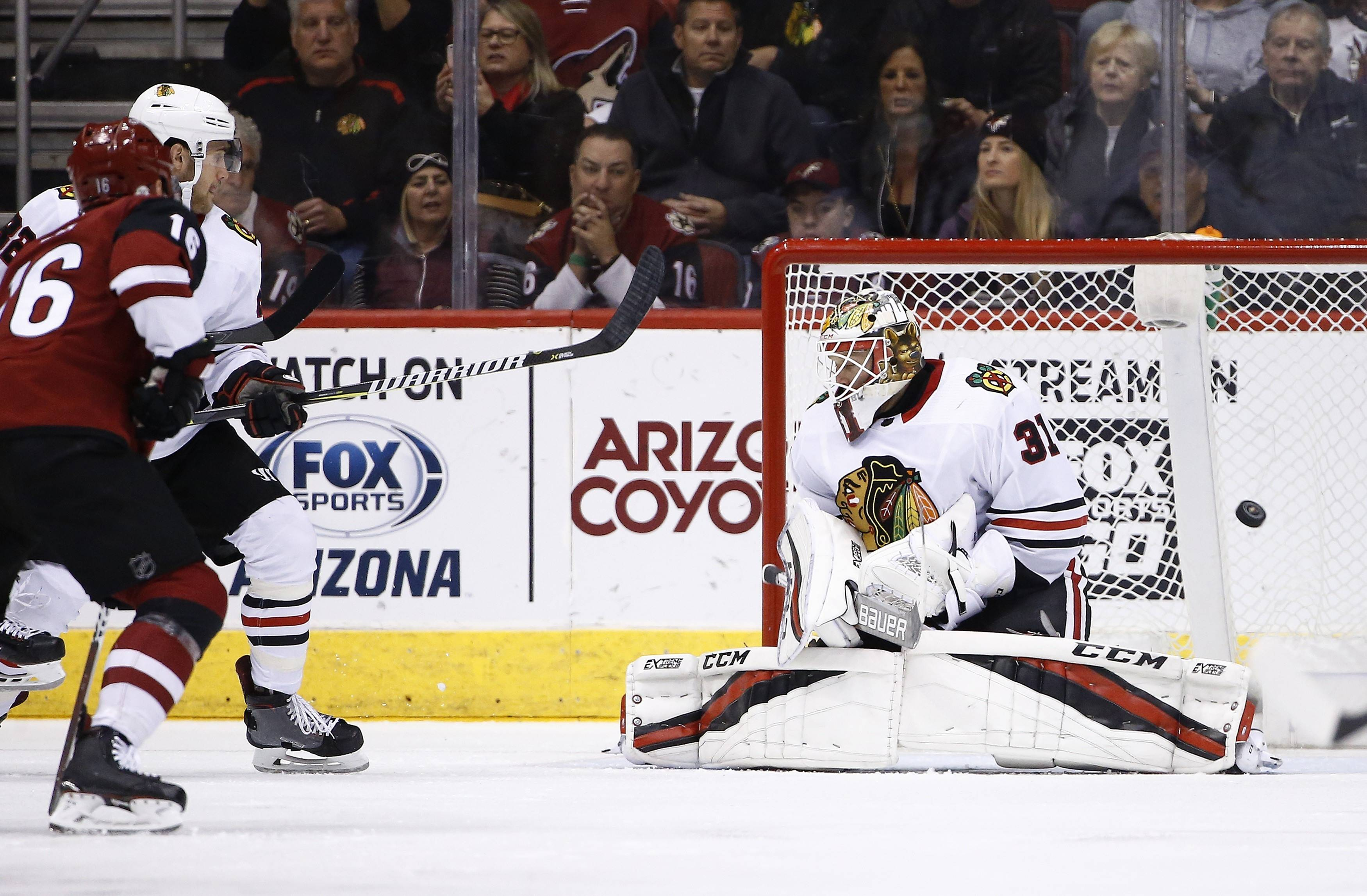 Arizona Coyotes left wing Max Domi (16) beats Chicago Blackhawks goaltender Anton Forsberg (31) for a goal as Blackhawks' Chicago Blackhawks defenseman Jordan Oesterle, back left, looks on during the first period of an NHL hockey game Monday, Feb. 12, 2018, in Glendale, Ariz.