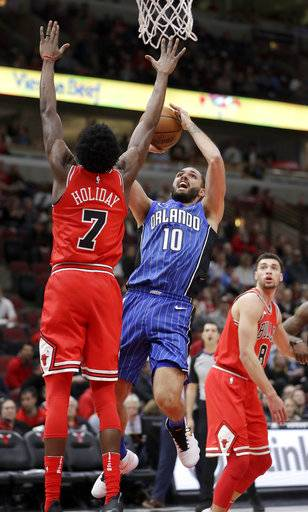 Orlando Magic's Evan Fournier (10) shoots over Chicago Bulls' Justin Holiday (7) as Zach LaVine watches during the first half of an NBA basketball game Monday, Feb. 12, 2018, in Chicago.