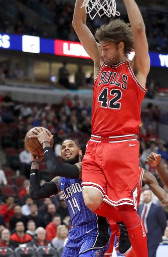 Orlando Magic's D.J. Augustin (14) gets Chicago Bulls' Robin Lopez off his feet for a foul during the first half of an NBA basketball game Monday, Feb. 12, 2018, in Chicago.