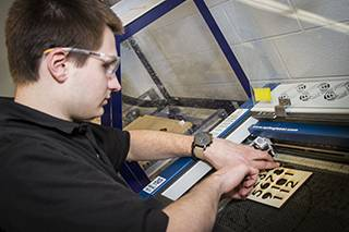 Dominic Olesak, an engineering student, uses a laser cutter in the Baxter Innovation Lab on the College of Lake County's Grayslake Campus in 2017. Olesak is now a civil engineering major at the University of Wisconsin-Platteville.