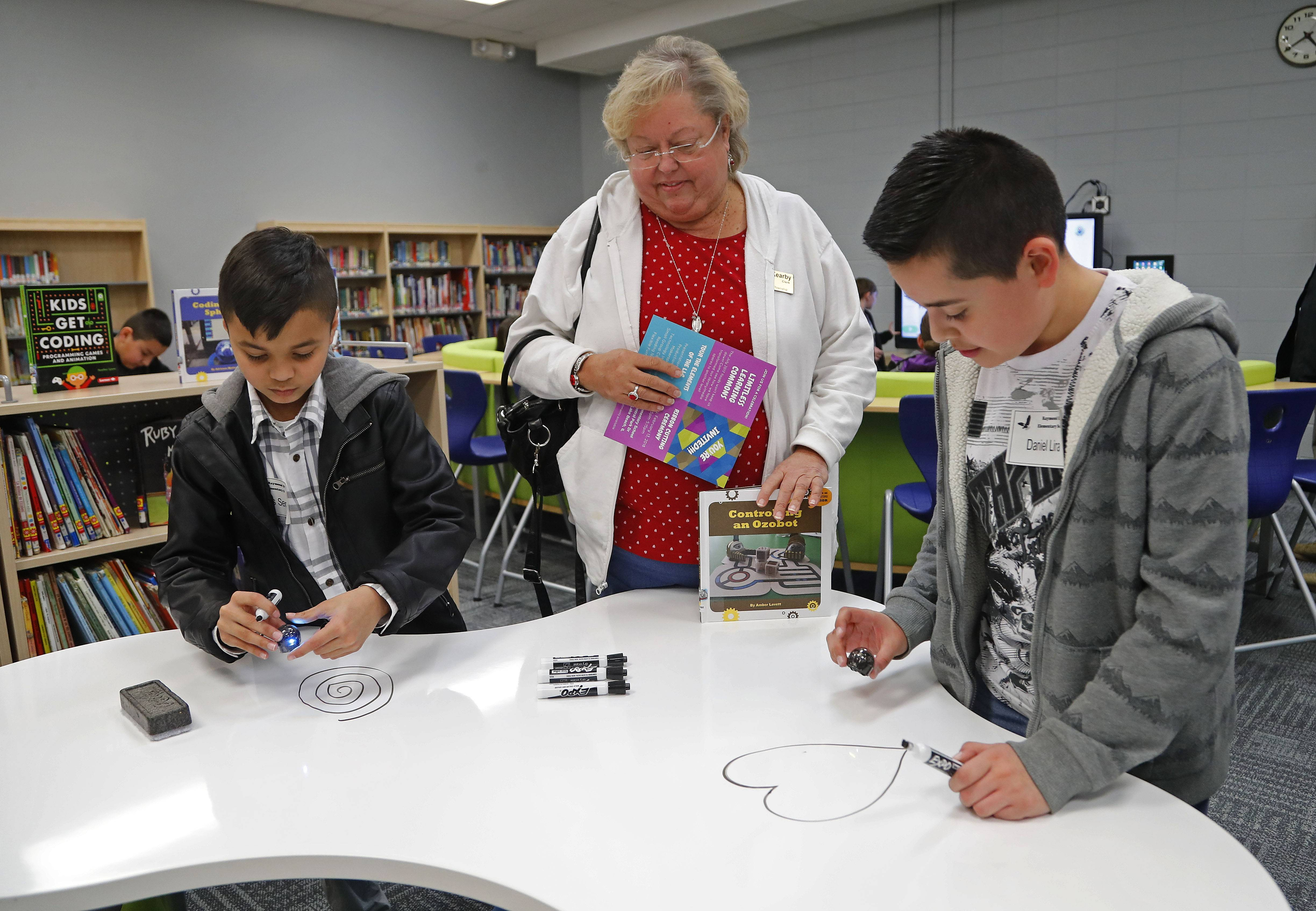 Steve Lundy/slundy@dailyherald.comEllis Elementary School students Nerkis Sena, 10, left, and Daniel Lira, 11 show Jeanne Kearby of Round Lake a dry erase table during a celebration to unveil their new Limitless Learning Commons Tuesday in Round Lake Beach.