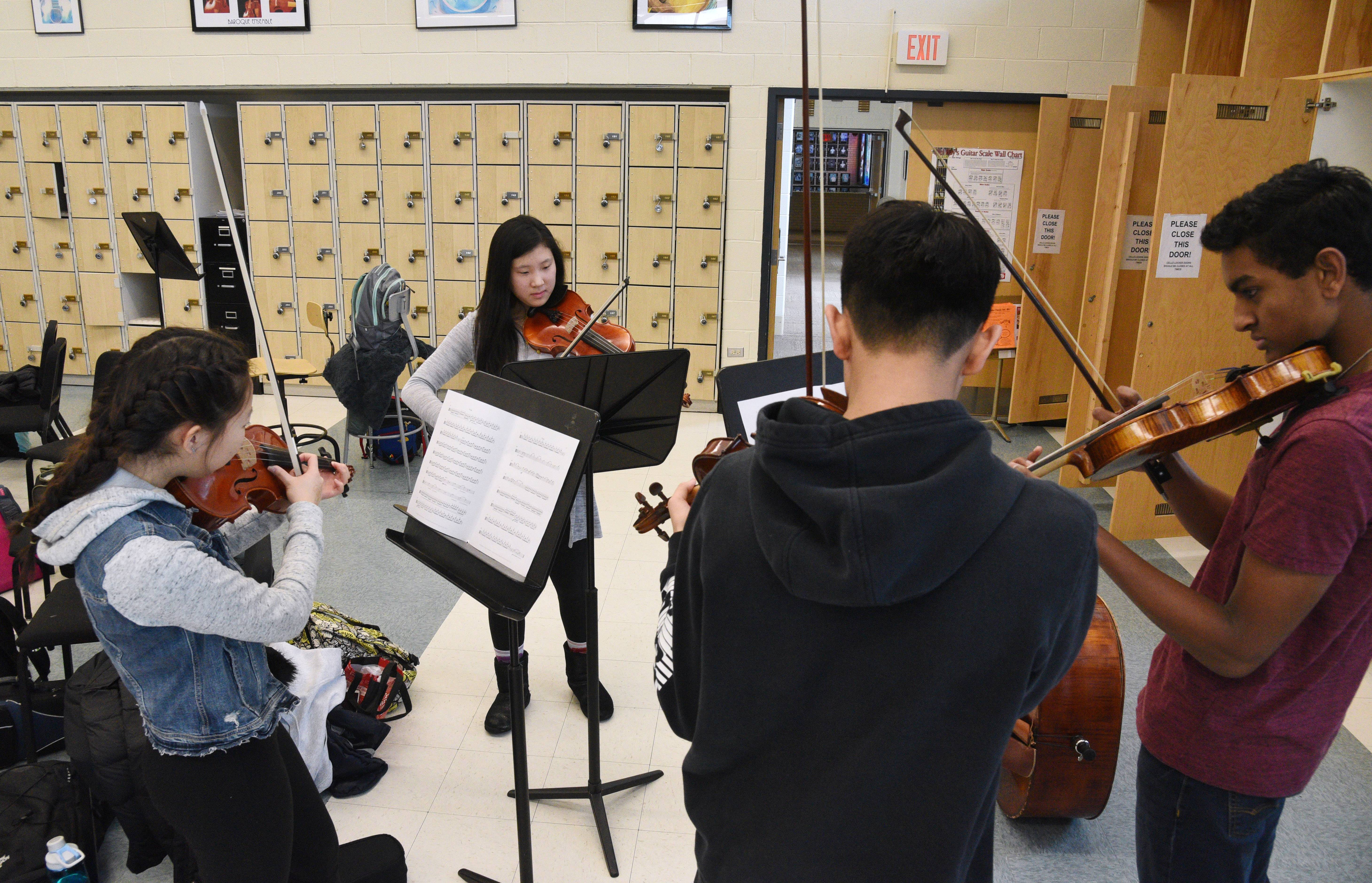 Stevenson High School concert orchestra members Christine Kim, Melissa Liu, Josh Chae and Justin Kuncheria rehearse at the Lincolnshire school Tuesday. Instrument storage space and lockers will be reconfigured this summer.