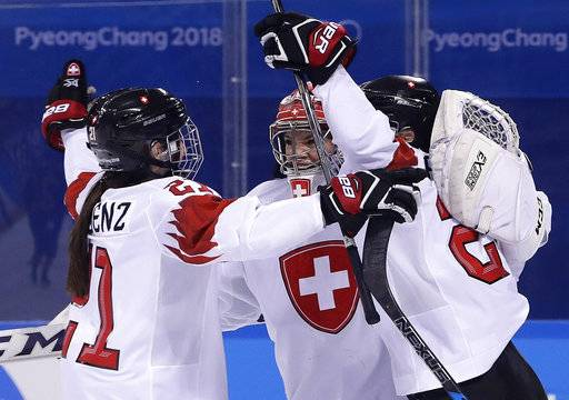 Laura Benz (21), goalie Florence Schelling (41) and Livia Altmann (22), of Switzerland, celebrate after the preliminary round of the women's hockey game Sweden at the 2018 Winter Olympics in Gangneung, South Korea, Wednesday, Feb. 14, 2018. Switzerland won 2-1.