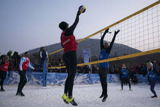 Brazil's Giba, center right, tries to block Austria's Stefanie Schwaiger during a snow volleyball exhibition match at the Austria House in Pyeongchang, South Korea, Wednesday, Feb. 14, 2018. Europe has a small snow volleyball league, and promoters showed off the sport in an exhibition match before hundreds of curiosity seekers.