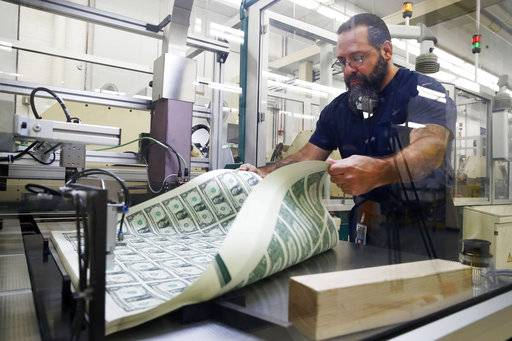 FILE- In this Nov. 15, 2017, file photo, Vincent Tacconelli aerates printed sheets of dollar bills, the first currency notes to bear the signatures of Treasury Secretary Steven Mnuchin and Treasurer Jovita Carranza at the Bureau of Engraving and Printing in Washington. Most economists expect inflation to edge up and end the year a few tenths of a percentage point above the Federal Reserve's target. But most foresee only minimal effect on the economy.