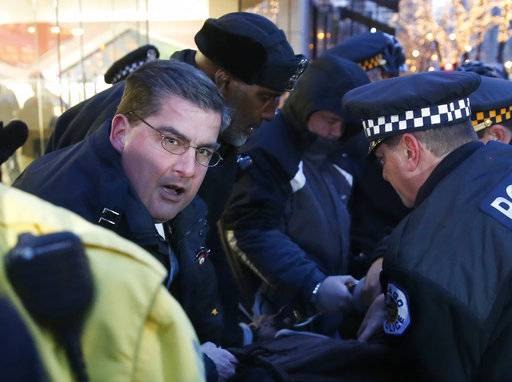In this Feb. 23, 2016 photo, then Chicago police Capt. Paul Bauer, left, takes part in the arrest of a protester outside an Apple store on Magnificent Mile in Chicago. Promoted to commander, Bauer, 53, a 31-year veteran of the department, was fatally shot Tuesday, Feb. 13, 2018, in downtown Chicago after he spotted a man matching the radio description of an armed suspect officers were chasing on foot, the city's police superintendent said.