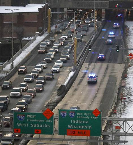 Law enforcement vehicles, right, travel West on the Eisenhower Expressway as part of a procession taking the body of Chicago Police Cmdr. Paul Bauer to the Cook County Medical Examiner's office Tuesday, Feb. 13, 2018, in Chicago. Bauer, who was off-duty, was shot several times when he went to assist tactical officers pursuing a fleeing suspect near the James R. Thompson Center In Chicago.