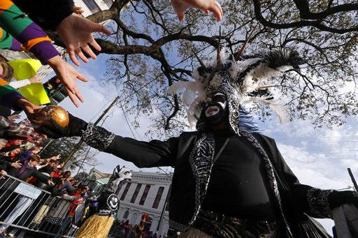 A member of the Crew of Zulu hands out prized painted coconuts as their parade rolls on Mardi Gras day in New Orleans, Tuesday, Feb. 13, 2018.