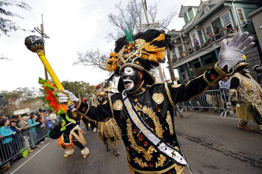 A member of the Krewe of Zulu marches during their parade Mardi Gras day in New Orleans, Tuesday, Feb. 13, 2018.