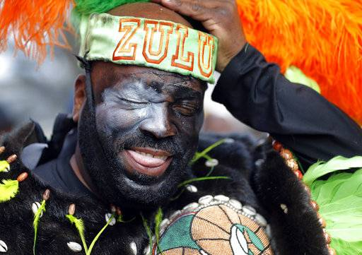 A member of the Krewe of Zulu adjusts his hat as their parade rolls on Mardi Gras day in New Orleans, Tuesday, Feb. 13, 2018.