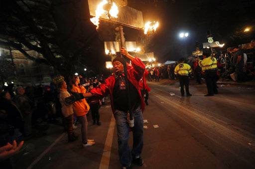 Flambeaux's cary their torches in the Krewe of Orpheus in New Orleans, Monday, Feb. 12, 2018. Tens of thousands of revelers are expected on New Orleans streets for parades and rowdy fun as Mardi Gras caps the Carnival season in a city with a celebration of its own, its 300th anniversary.