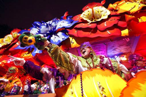 Float riders toss trinkets as the Krewe of Orpheus rolls in New Orleans, Monday, Feb. 12, 2018.