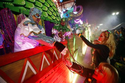 Float riders hand beads to the crowd as the Krewe of Orpheus rolls in New Orleans, Monday, Feb. 12, 2018. Tens of thousands of revelers are expected on New Orleans streets for parades and rowdy fun as Mardi Gras caps the Carnival season in a city with a celebration of its own, its 300th anniversary.
