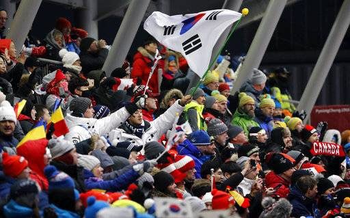 Fans wave flags during the women's luge final at the 2018 Winter Olympics in Pyeongchang, South Korea, Tuesday, Feb. 13, 2018.