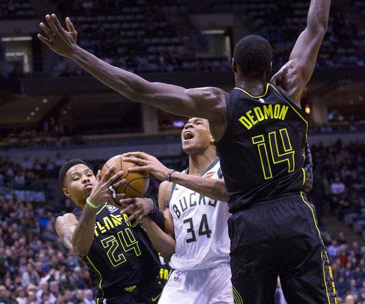 Milwaukee Bucks forward Giannis Antetokounmpo, center, is defended by Atlanta Hawks guard Kent Bazemore, left, and Dewayne Dedmon, right, during the first half of an NBA basketball game Tuesday, Feb. 13, 2018, in Milwaukee.
