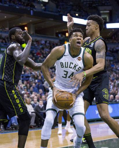 Milwaukee Bucks forward Giannis Antetokounmpo, center, is defended by Atlanta Hawks guard Kent Bazemore, left, and John Collins, right, during the first half of an NBA basketball game Tuesday, Feb. 13, 2018, in Milwaukee.