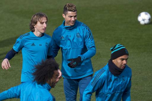 Real Madrid's Cristiano Ronaldo, center, smiles next to Luka Modric, left, during a training session in Madrid, Spain, Tuesday Feb. 13, 2018. Real Madrid will play Paris Saint Germain Wednesday in a Round of 16, 1st leg Champions League soccer match.