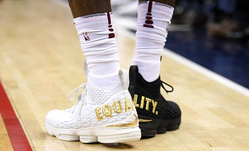 "FILE - In this Dec. 17, 2017, file photo, Cleveland Cavaliers forward LeBron James' shoes are emblazoned with ""EQUALITY"" on both heels during the first half of an NBA basketball game against the Washington Wizards, in Washington. When LeBron James stepped on the court wearing mismatched sneakers in the nation's capital, it wasn't a fashion statement by the NBA's most popular athlete. The message was clearly emblazed in gold on the back of his kicks. Sneaker enthusiasts around the world eagerly await NBA All-Star weekend when new and limited editions of the latest shoes make their debut, but the month leading up to highly anticipated shoe palooza is a time often used to make a social statement."