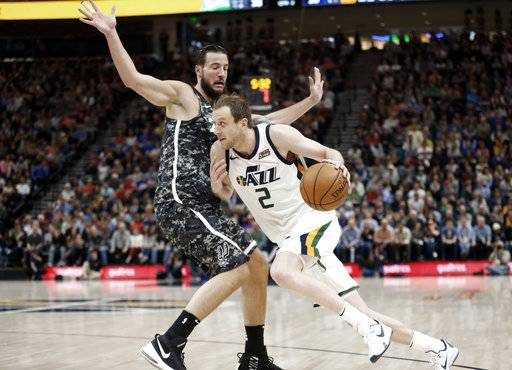 Utah Jazz forward Joe Ingles (2) drives around San Antonio Spurs center Joffrey Lauvergne in the first half of an NBA basketball game Monday, Feb. 12, 2018, in Salt Lake City.