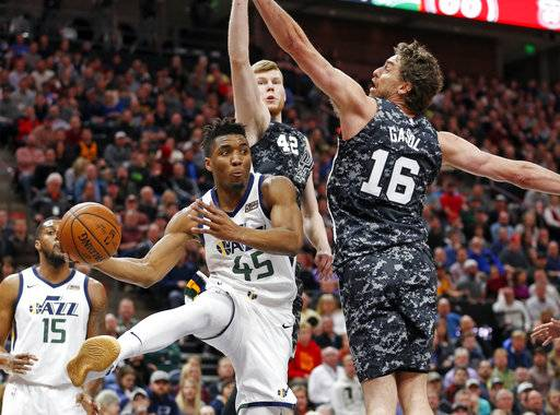 San Antonio Spurs' Davis Bertans (42) and Pau Gasol (16) defend against Utah Jazz guard Donovan Mitchell (45) in the first half of an NBA basketball game Monday, Feb. 12, 2018, in Salt Lake City.