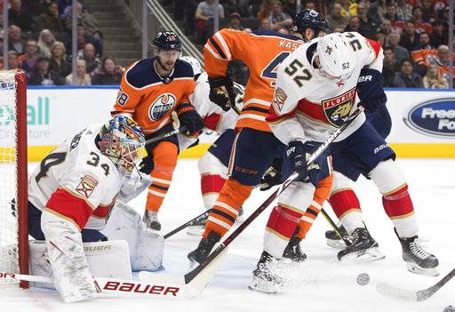 Florida Panthers goaltender James Reimer (34) makes the save as defenseman MacKenzie Weegar (52) and Edmonton Oilers right wing Zack Kassian (44) battle in front during second period NHL hockey action in Edmonton, Alberta, Monday Feb. 12, 2018. (Jason Franson/The Canadian Press via AP)