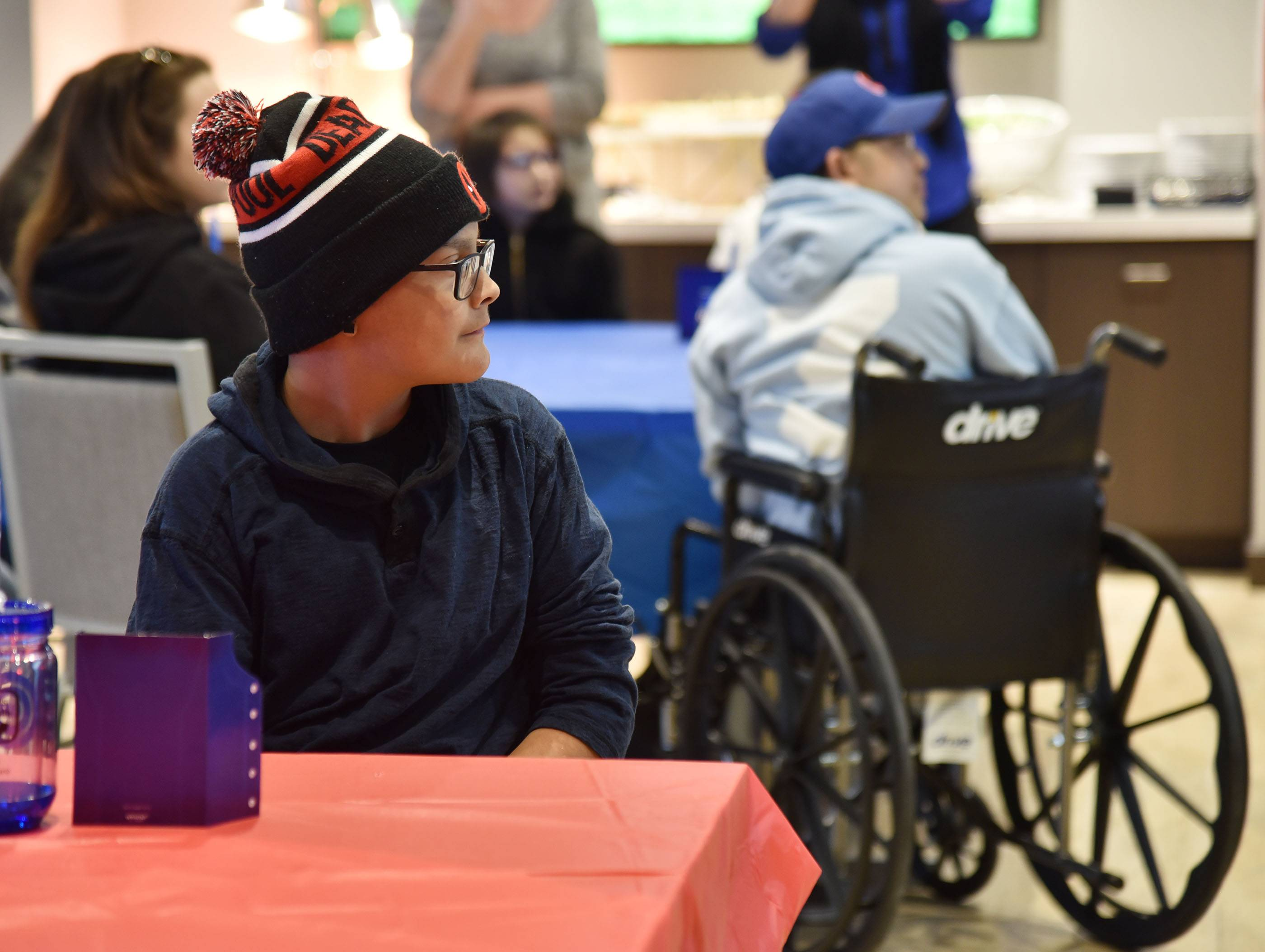 Jonathan Olmos, 16, of Des Plaines, foreground, and Zachary Lum, 17, of Sleepy Hollow watch a video during an event Wednesday at Wrigley Field where they were surprised with a trip to see the Chicago Cubs in spring training in Arizona. They are among a group of four teens, who are patients at Advocate Children's Hospital in Park Ridge being treated to the all-expenses-paid trip.