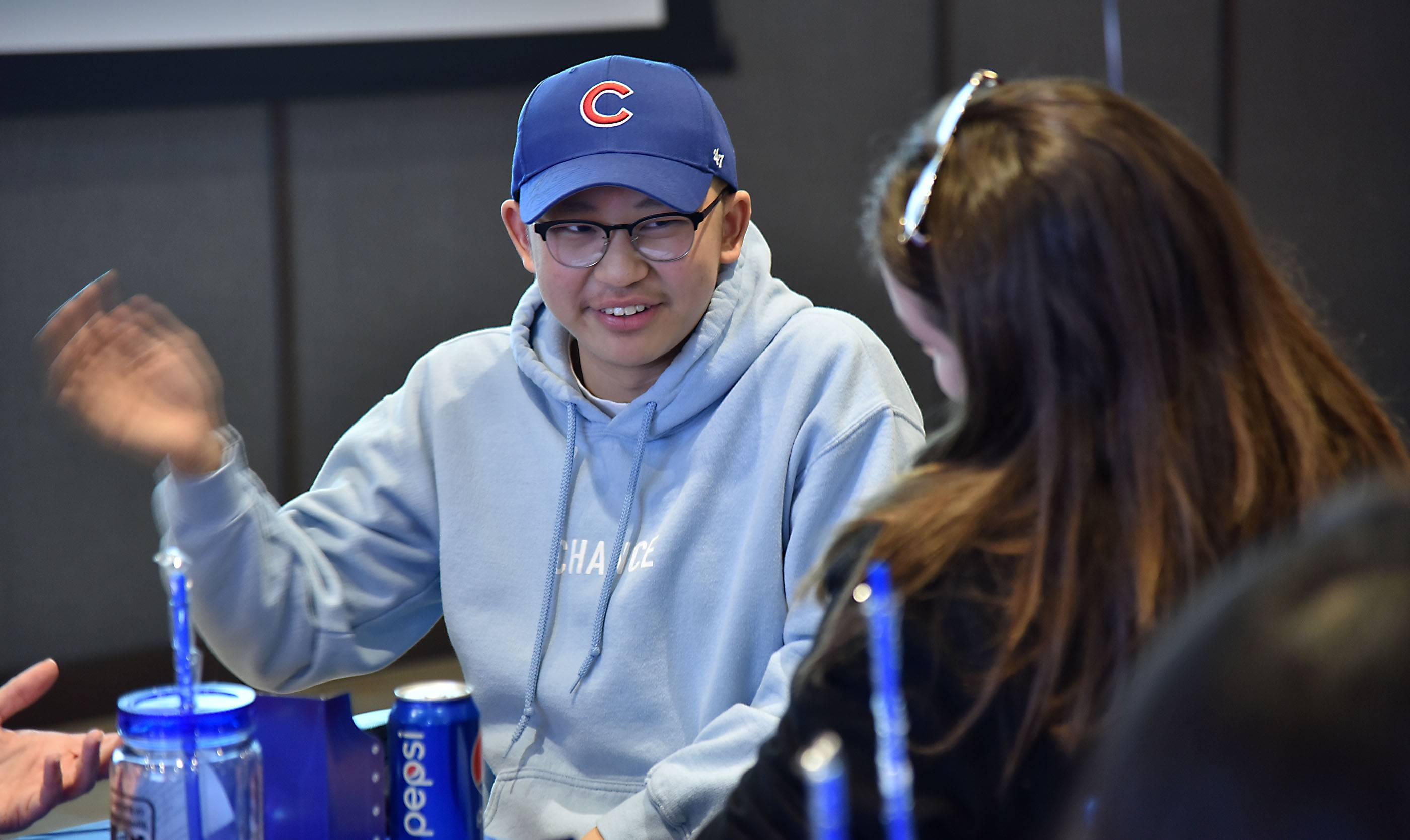 Zachary Lum, 17, of Sleepy Hollow talks with his friend, Tori Redmond, a Jacobs High School student, Wednesday at Wrigley Field. Lum is one of four patients at Advocate Children's Hospital in Park Ridge, who will bring their families and a friend on an all-expenses-paid trip to see the Chicago Cubs in spring training in Arizona.