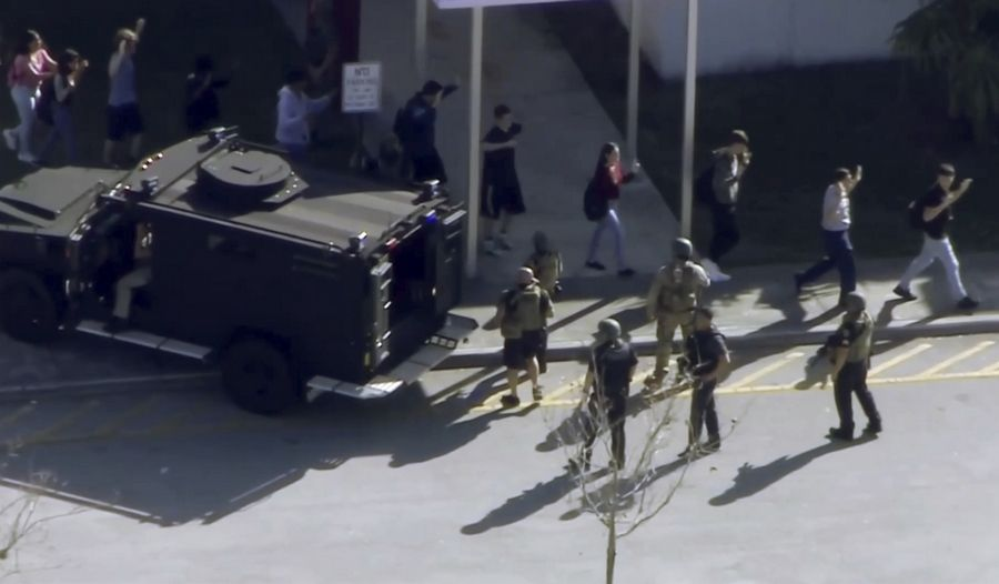 In this frame grab from video provided by WPLG-TV, students from the Marjory Stoneman Douglas High School in Parkland, Florida, evacuate the school Wednesday after a shooting.