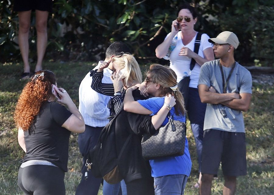Anxious family members wait for news of students as two people embrace, Wednesday in Parkland, Fla. A shooting at Marjory Stoneman Douglas High School sent students rushing into the streets as SWAT team members swarmed in and locked down the building.