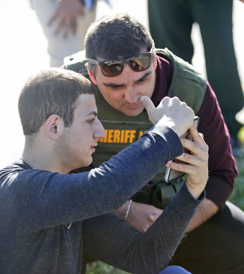 A student shows a law enforcement officer a photo or video from his phone, Wednesday, Feb. 14, 2018, in Parkland, Fla. A shooting at Marjory Stoneman Douglas High School sent students rushing into the streets as SWAT team members swarmed in and locked down the building.