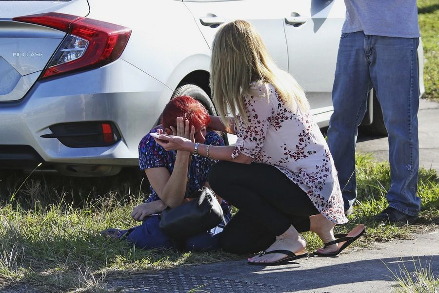 A woman consoles another as parents wait for news regarding a shooting at Marjory Stoneman Douglas High School in Parkland, Fla., Wednesday,.