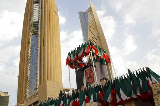A picture of Kuwait's ruling emir, Sheikh Sabah Al Ahmad Al Sabah, is displayed with surrounding Kuwaiti flags in Kuwait City, Kuwait, Wednesday, Feb. 14, 2018. Kuwait on Wednesday hosted the final day of a conference seeking billions of dollars to help rebuild Iraq after the war against the Islamic State group.