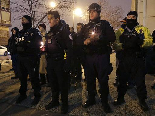 Chicago police officers gather for a candlelight vigil for police Cmdr. Paul Bauer outside the Near North District headquarters Wednesday, Feb. 14, 2018, in Chicago. The 53-year-old Bauer, who had been with the department 31 years, was fatally shot as he went to assist other officers who were pursuing the suspect, Shomari Legghette, in downtown Chicago on Tuesday. Legghette is charged with first-degree murder in the shooting of Bauer.