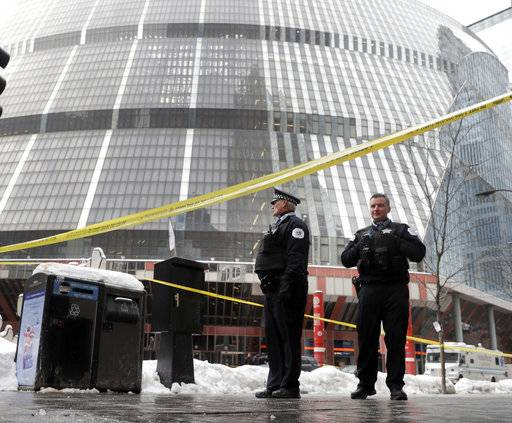 Chicago police officers remain on the scene outside the James R. Thompson Center after off-duty Police Cmdr. Paul Bauer was shot several times as he went to assist tactical officers pursuing a fleeing suspect near the center on Tuesday, Feb. 13, 2018, in Chicago.