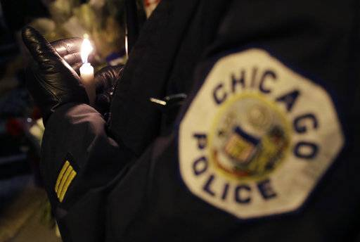 A Chicago police officer shields their candle from the wind as they attend a candlelight vigil for police Cmdr. Paul Bauer outside the Near North District headquarters Wednesday, Feb. 14, 2018, in Chicago. The 53-year-old Bauer, who had been with the department 31 years, was fatally shot as he went to assist other officers who were pursuing the suspect, Shomari Legghette, in downtown Chicago on Tuesday. Legghette is charged with first-degree murder in the shooting of Bauer.