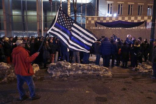 James Poole holds a police memorial American flag as he attends a candlelight vigil for Chicago Police Cmdr. Paul Bauer outside the Near North District headquarters Wednesday, Feb. 14, 2018, in Chicago. The 53-year-old Bauer, who had been with the department 31 years, was fatally shot as he went to assist other officers who were pursuing the suspect, Shomari Legghette, in downtown Chicago on Tuesday. Legghette is charged with first-degree murder in the shooting of Bauer.