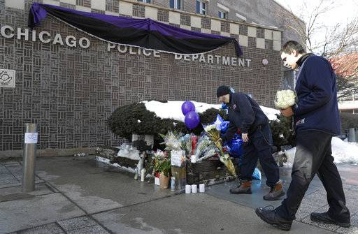 Todd Markshon, left, and Nick Moulopoulos bring flowers to a memorial for Chicago Police Cmdr. Paul Bauer outside the Near North District headquarters, Wednesday, Feb. 14, 2018, in Chicago. Bauer, 53, a 31-year veteran of the department was shot several times as he went to assist tactical officers pursuing a fleeing suspect in downtown Chicago Tuesday.