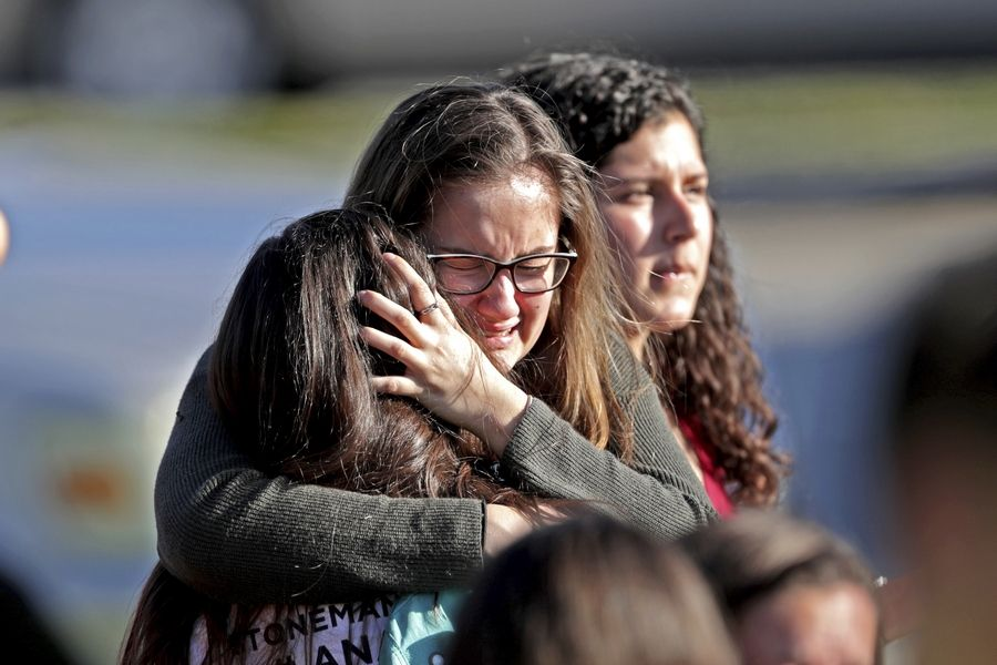 Students released from a lockdown embrace Wednesday following following a shooting at Marjory Stoneman Douglas High School in Parkland, Florida.