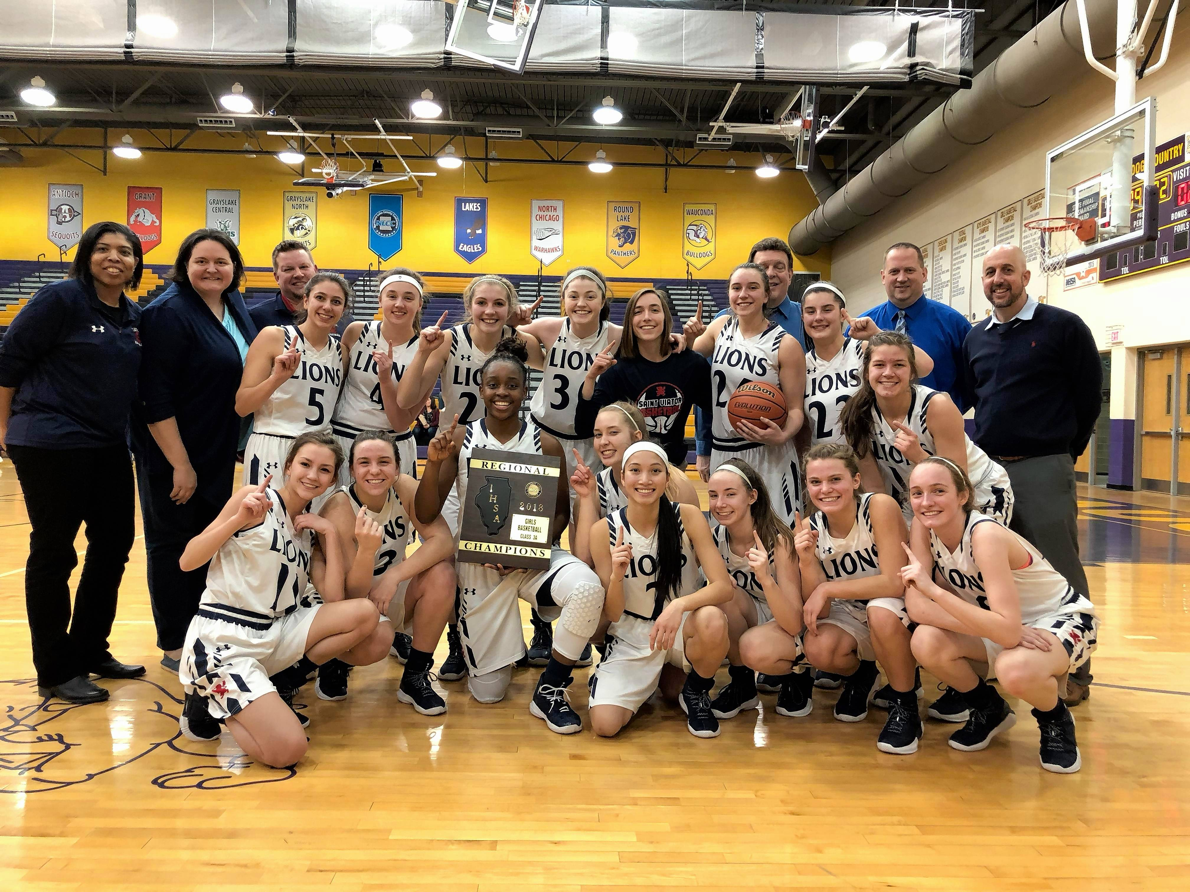 St. Viator's girls basketball team celebrates its Class 3A regional championship Thursday at Wauconda.