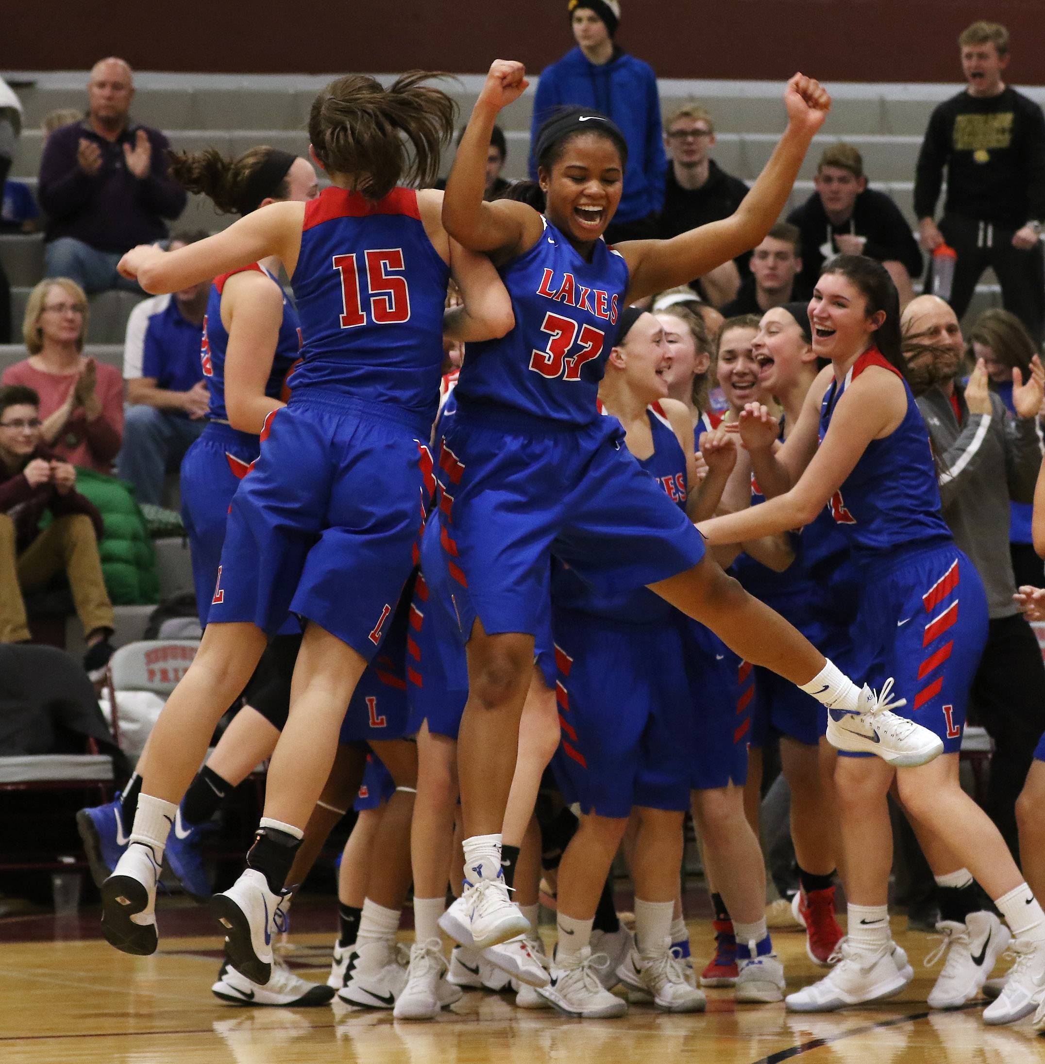 Lakes players Sara Smith, left, bumps with Brittany Washington as they celebrate their victory. Lakes won the game 46 - 38.
