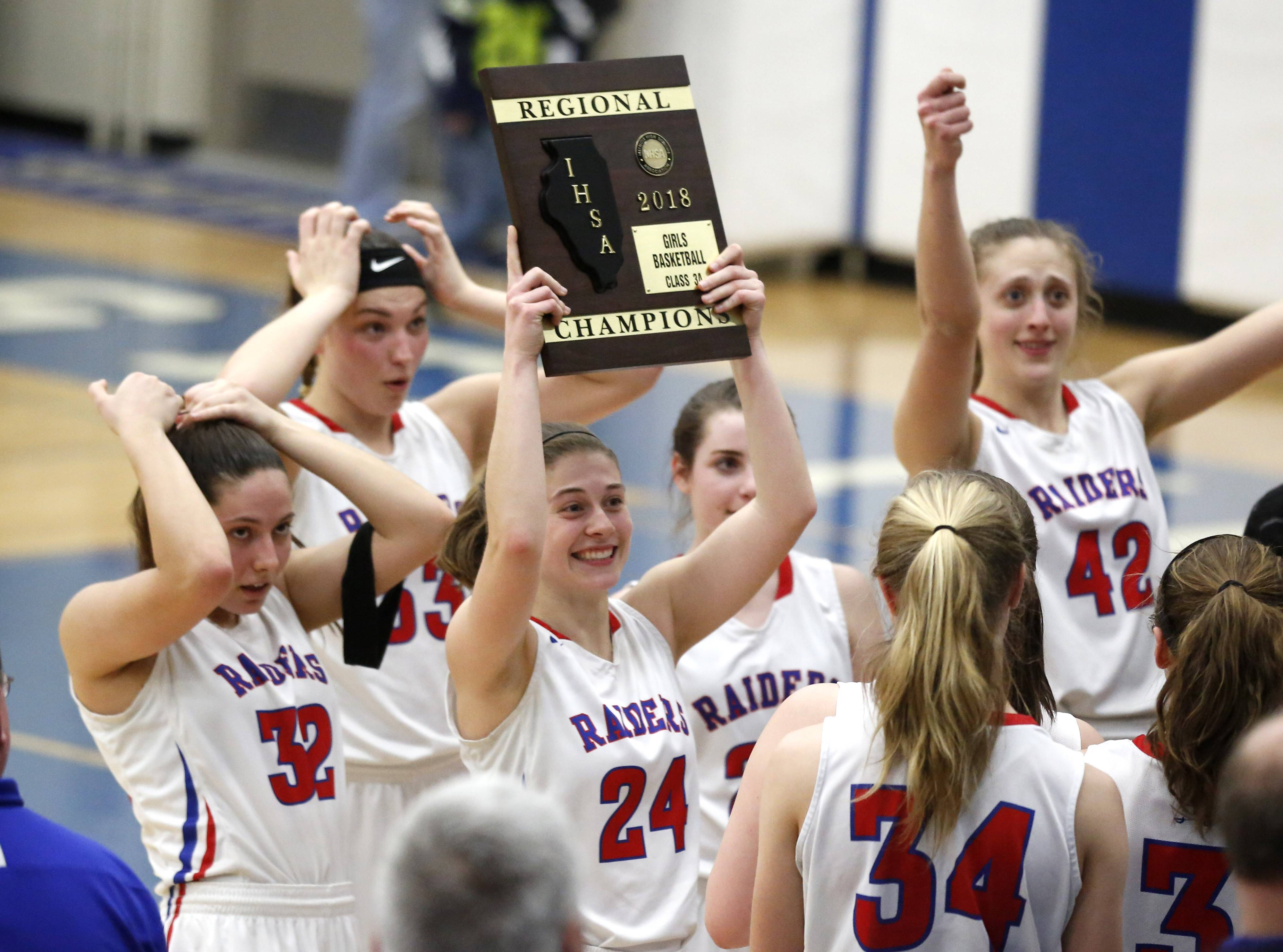 Glenbard South's Sarah Cohen (24) holds up the Class 3A girls basketball championship plaque after defeating St. Francis 51-39 in Wheaton.