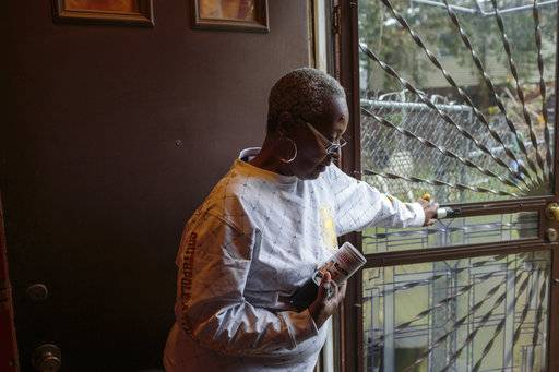 ADVANCE FOR USE THURSDAY, FEB. 15, 2018, AT 12:01 A.M. AND THEREAFTER -This Nov. 13, 2017, photo provided by Reveal, Adrienne Stokes, a longtime resident of Philadelphia's historically black Point Breeze neighborhood, stands inside her home. In 2015, Stokes was denied a home improvement loan at her local bank, Firstrust Savings Bank. (Sarah Blesener/Reveal via AP)