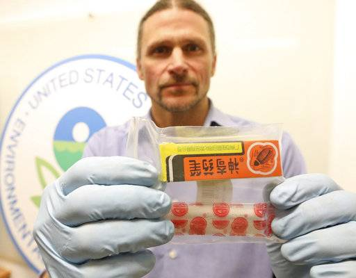 Environmental Protection Agency enforcement officer Chad Schulze displays, Thursday, Feb. 15, 2018, in Seattle, one of the banned pesticides that investigators say was listed for sale on Amazon. The EPA on Thursday announced a $1.2 million settlement with Amazon over the sale and distribution of illegal pesticides, one of the largest penalties assessed under federal pesticides laws. (Greg Gilbert/The Seattle Times via AP)