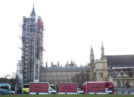 The Community-led organisation, Justice4Grenfell, parades three billboards past the Houses of Parliament in London Thursday Feb. 14, 2018, calling for justice for the victims of the June 14, 2017, deadly apartment fire.  Campaigners for victims of the deadly London Grenfell Tower high-rise apartment fire have taken inspiration from an Academy Award-nominated film to press for more action by police. (Jeff Moore/Justice4Grenfell via AP)